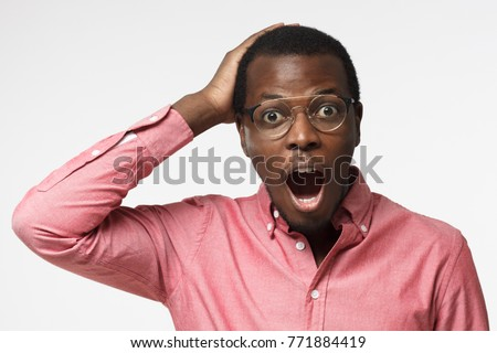 Casual dressed young african businessman in pink shirt shouting oh my god with open mouth, surprised by low price and sales, isolated on gray background #771884419