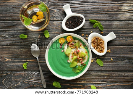 Bowl with green spirulina smoothie on table. Healthy vegan food concept #771908248