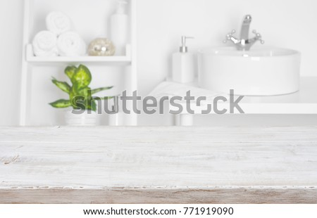 Wooden table over blurred spa salon bathroom shelves background #771919090
