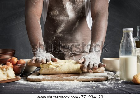 Image of hard working male cook or baker with dark skin wears apron, sheets well made dough, going to bake tart, isolated over black chalk background. Unrecognizable African American chef on kitchen #771934129