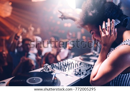 Young woman playing music at the club Royalty-Free Stock Photo #772005295
