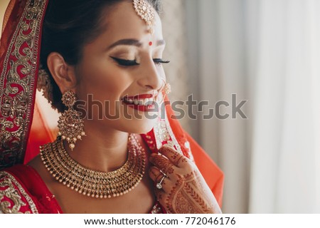 Stunning Indian bride dressed in Hindu red traditional wedding clothes lehenga embroidered with gold and a veil smiles tender #772046176