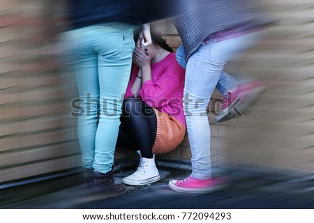 Teenage girls bullying and kicking a girl sitting down covering her face, crying. Blurred. #772094293