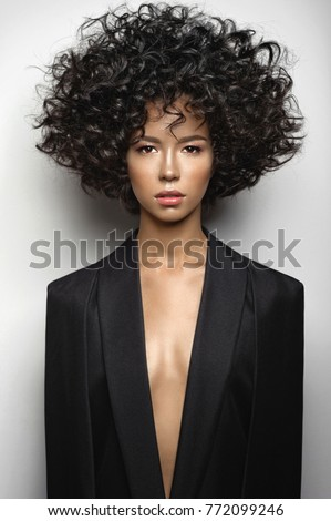 Fashion studio portrait of beautiful woman in black cape with afro curls hairstyle. Fashion and beauty #772099246