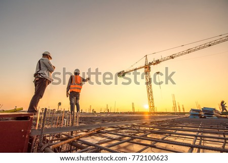 Construction engineers supervising progress of construction project stand on new concrete floor top roof and crane background #772100623