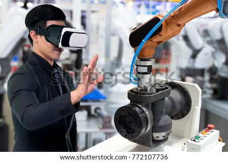 Virtual reality technology in industry 4.0. Business man suit wearing VR glasses to see AR service , Thermal Monitoring motor for check destroy part of smart robot arm machine in smart factory. #772107736