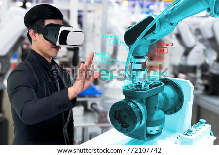 Virtual reality technology in industry 4.0. Business man suit wearing VR glasses to see AR service , Thermal Monitoring motor for check destroy part of smart robot arm machine in smart factory. #772107742