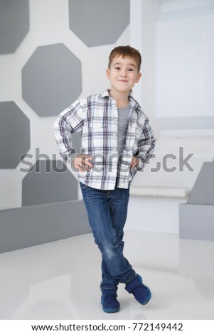A boy in a plaid shirt in full growth indoors. #772149442