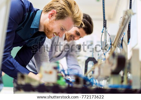 Two young handsome engineers working on electronics components #772173622
