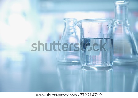 experiment water in beaker and flask in blue chemistry science laboratory background Royalty-Free Stock Photo #772214719