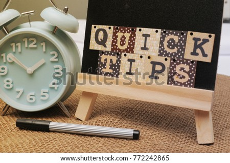 Quick Tips Concept.Book, pen and alphabet blocks with QUICK TIPS inscription on chalkboard with vintage canvas sack background. #772242865