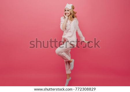 Full-length portrait of winsome girl in pajamas and socks dancing on pink background. Studio shot of graceful caucasian female lady in eyemask having fun in morning. #772308829