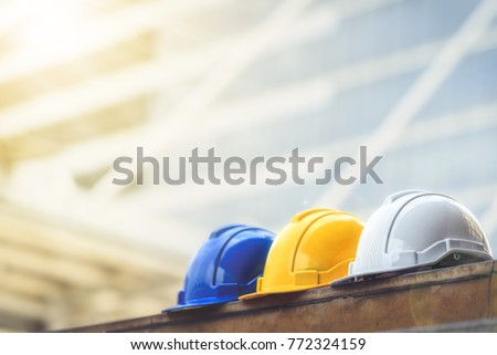 white, yellow and blue hard safety helmet hat for safety project of workman as engineer or worker, on concrete floor on city. Royalty-Free Stock Photo #772324159