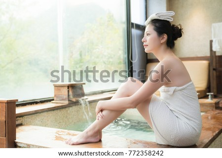beautiful japan girl put towels on her head to reduce body temperature and enjoy the view sitting on poolside of hot springs #772358242