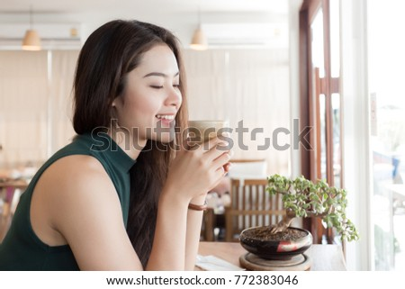 Young happy Asian woman drinking coffee in the coffee shop. #772383046