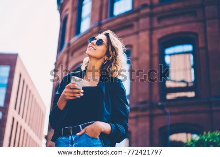 Positive hipster girl in sunglasses enjoying spring day using mobile for chatting in social networks, smiling young woman dressed in stylish outfit feeling excited with spending time outdoors #772421797
