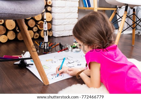 Young child girl female painting astronaut costume by colorful pens and dreaming about cosmos with cosmonaut constructor toys: rocket, shuttle and rover in comfortable interior at home on wooden floor #772466779