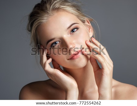 Attractive young girl touching her lips. Photo of blonde girl with perfect skin on grey background. Beauty & Skin care concept
