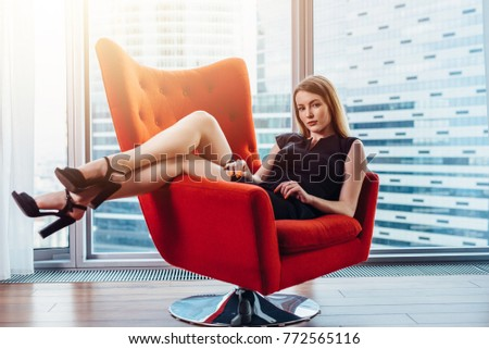 Portrait of sexy businesswoman relaxing in stylish armchair at office #772565116