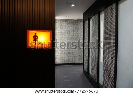 Public female restroom. Yellow light box of modern women toilet's sign on wall at the entrance way in Tokyo, Japan. Lady toilet sign concept.