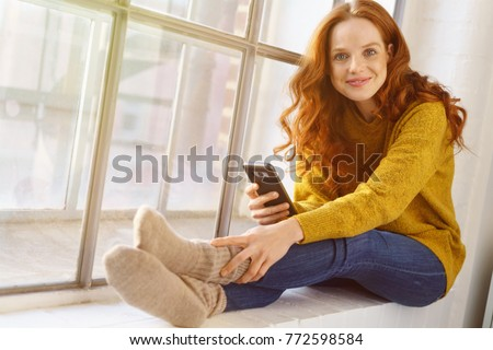 Portrait of young red-haired smiling woman sitting on windowsill with mobile phone #772598584