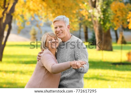 Cute elderly couple dancing in autumn park #772617295