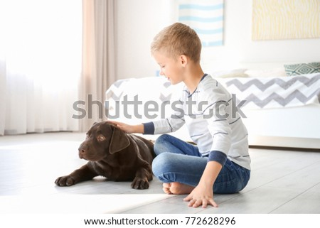 Cute little boy with dog on floor at home #772628296
