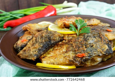 Pieces of fried fish (carp) on a ceramic plate on a dark wooden background. #772642468