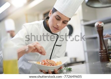 Closeup of cook chef in professional kitchen preparing dish #772649605