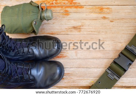 Military back pack for soldier,Military combat boots,Army water canteen on wooden background,top view for copy space