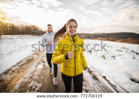 Beautiful happy active runner girl jogging with her personal handsome trainer on a snowy road in nature. #772706119
