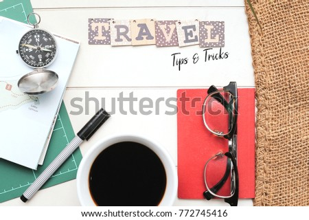 Travel Tips and Tricks.Book,Passport,pen,Coffee,navigation compass and a map on the white table with vintage canvas sack written with words TRAVEL TIPS AND TRICKS.