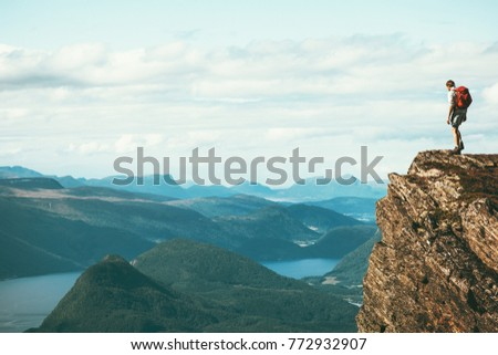 Man explorer standing on cliff alone mountain summit over fjord Norway landscape Travel Lifestyle success motivation concept adventure active vacations outdoor #772932907
