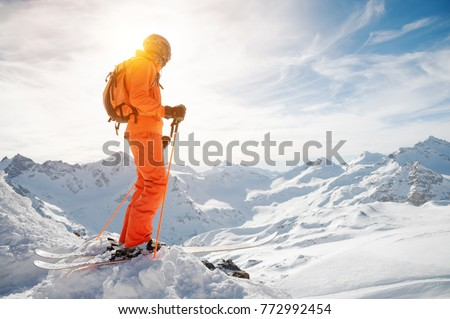 A skier in an orange overall with a backpack on his back wearing a helmet and with ski poles in his hands is standing on a precipice in front of a snowy abyss in the background of a beautiful #772992454