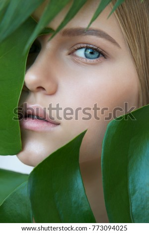Face of beautiful young woman with clean perfect skin covered by leaves. Portrait of beauty model with natural nude make up and long eyelashes. Spa, skincare and wellness. Close up. #773094025