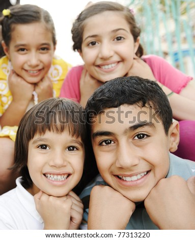 Vertical photo of children group, four friends smiling outdoor, boys and girls closeup #77313220