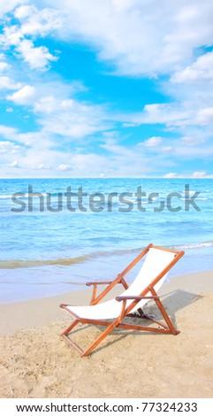 An empty chair on a sandy beach near the water #77324233