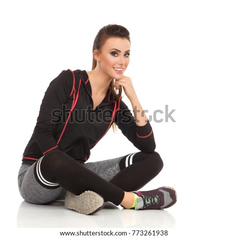 Beautiful young woman in fitness clothes is sitting on floor legs crossed, looking at camera and smiling. Full length studio shot isolated on white. #773261938