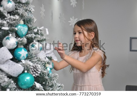 Little girl decorating a Christmas tree. Smiling girl finishing decorations for New Year holidays #773270359