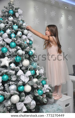 Little girl decorating a Christmas tree. Smiling girl finishing decorations for New Year holidays #773270449