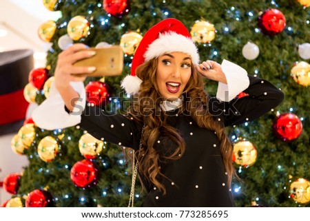 funny young Christmas girl taking selfie photo with mobile phone near Christmas tree