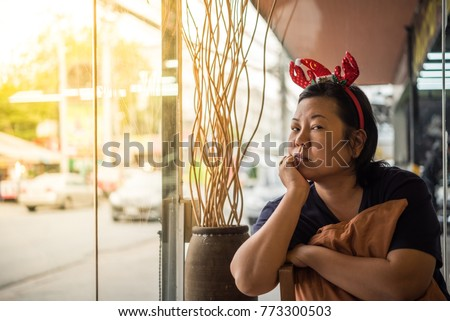 Asian woman 40s white skin have a lovely thao chin gesture wait for something in a coffee shop cafe with santa claus headband in merry christmas and new year celebration #773300503