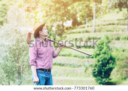 young farmer in field is holding hoe while working in his mountain farming land in chiang mai thailand - people in local small farming business concept  #773301760