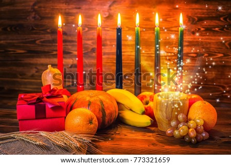 Kwanzaa holiday concept with traditional lit candles, gift box, pumpkins, ears of wheat and miracle magic light on wood background