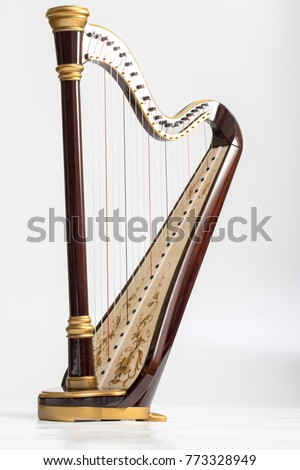 Celtic irish harp, classical and traditional string music instrument, isolated white background #773328949