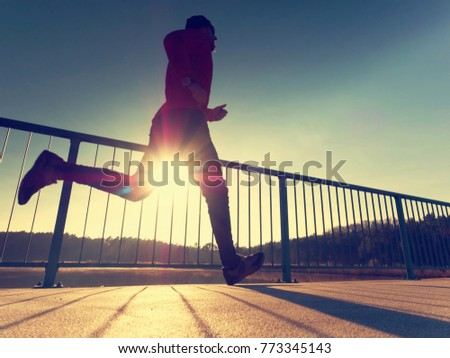 Morning runner in tall black leggings exercising  on bridge. Outdoor exercising on smooth concrete ground on lake bridge. Sun is outlining man body #773345143