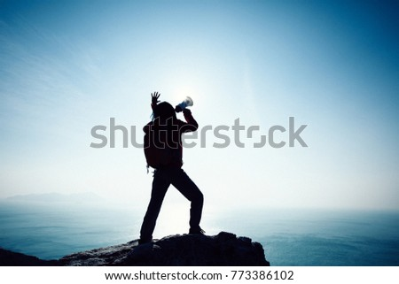 Young woman shouting with loudspeaker on windy sunrise coast cliff edge #773386102