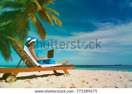 young woman with laptop on tropical beach #773389675