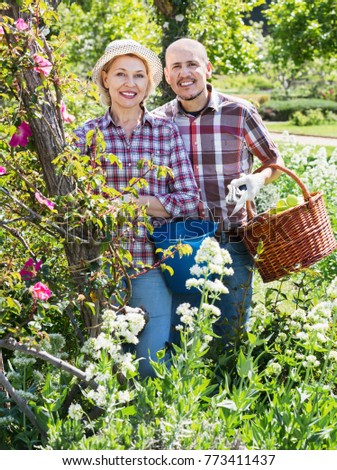 Ordinary cheerful  senior couple looking after flowers in the garden #773411437