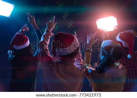 Group Asian young friends dancing Together party with Disco lights celebrating Christmas at dark home, Christmas or New Year concept #773421973